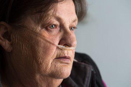 Tired woman using supplemental oxygen for pulmonary illness